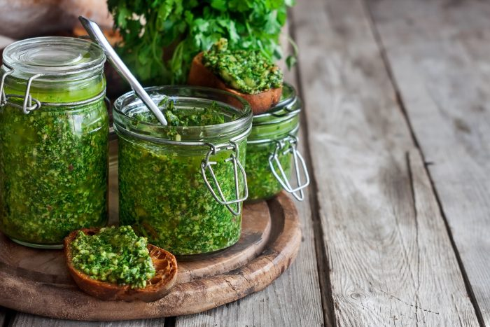 Homemade cilantro pesto in jars on wooden background